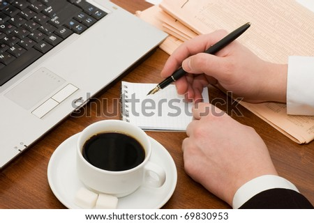 The businessman behind a cup from coffee