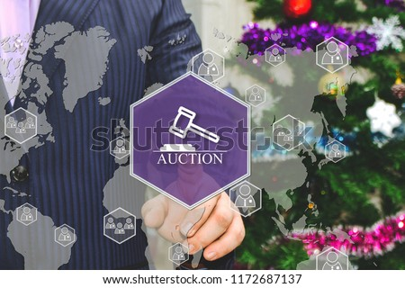 The businessman chooses AUCTION on the touch screen, the backdrop of the Christmas tree and decorations. Special toning