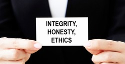 The businessman holds a business card with the text OF INTEGRITY, HONESTY, ETHICS.