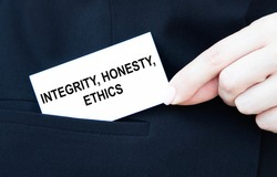 The businessman puts in his pocket a business card with integrity, HONESTY, ETHICS.