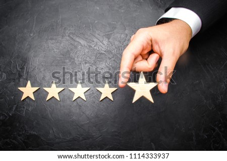 The businessman's hand in the suit holds the fifth star. Get the fifth star. The concept of the rating of hotels and restaurants, the evaluation of critics and visitors. Quality level, Selective focus