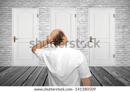 The businessman stands in a room and thinks