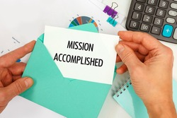 The businessman takes out a card from the envelope with the text Mission Accomplished, on the background of the office desk.