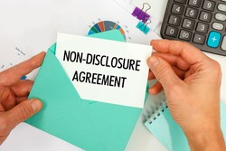 The businessman takes out a card from the envelope with the text Non-Disclosure Agreement, on the background of the office desk.