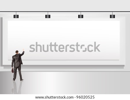 The businessman with a portfolio against an advertising billboard