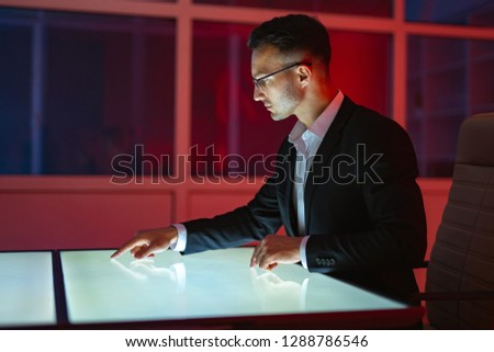 The businessman working with a touchscreen in the red room #1288786546
