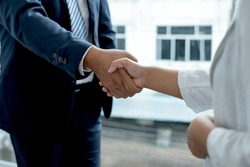 The businessmen shake hands after the meeting was successful and agreed upon.
