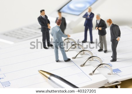 The businessmen who hold a meeting on the binder note and mobile phone.