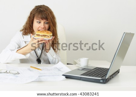 The businesswoman hurries up to eat without coming off office work