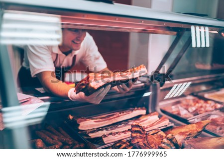 the butcher shows customers fresh bacon.Meat in focus Foto stock ©