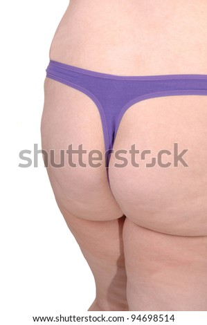 The butt of a overweight woman in a purple thong standing in the studio for white background.