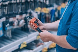 The buyer in the hardware store selects the goods. A man holds a wrench in his hand