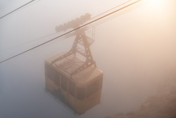 The cable car in Crimea Ai-Petri mountains in thick fog. View from the cliff to the cable car with a rising funicular, mountains in the clouds illuminated by the bright sun. Outdoors travel concept.