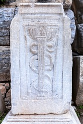 The Caduceus of Asclepius standing on the site of a public hospital. The snake on a rod. The Caduceus, universal symbol of medicine in ruins of Ephesus, Selcuk, Izmir, Turkey. UNESCO Heritage Site.