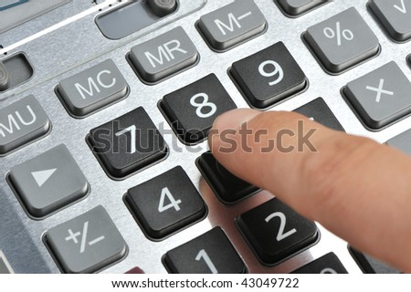 The calculator and a hand of the man. Pressing of a key of the calculator - stock photo