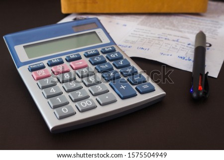The calculator is placed on the brown sofa cushion in the house. Calculate the cost of car repair equipment
