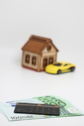 The calculator lies on European banknotes on the background of a yellow car, an accurate financial calculation