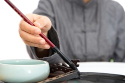 The calligrapher in Tang Dynasty clothes dipped ink in the inkstone with a brush