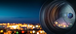 The camera lens on the background of the fiery city lights. Concept on the topic of news, media, information. Camera Lens background.