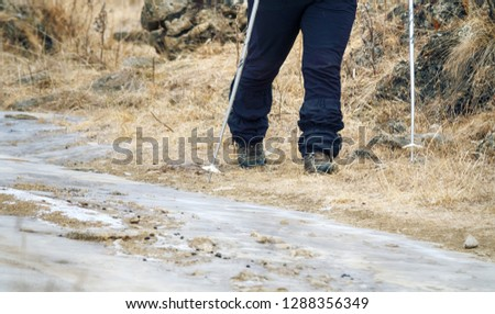 The camera takes off his feet in winter sportswear, hiking boots, trekking poles. Trekking in natural relief, walking on field road. #1288356349