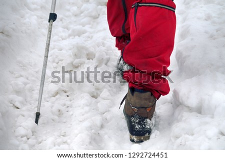 The camera takes off his feet in winter sportswear, hiking boots, trekking poles. Trekking in natural relief, walking on a snow-covered field road. #1292724451