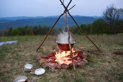The camping pot on the open fire in the nature with the blue mountains in the background during sunset. The photo of the campfire with the kettle on the horizon of the park.