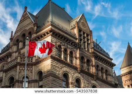 The Canadian flag flies before the Old City Hall in Toronto, Canada.