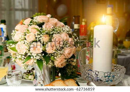 stock photo the Candles and wedding bouquet roses on a banquet table