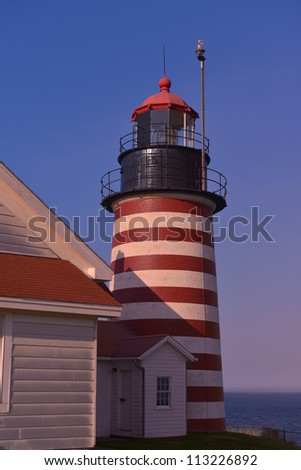 The candy striped light tower of the west Quoddy Lighthouse at sunset
