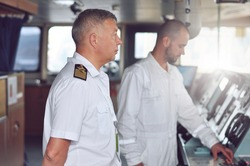 The captain of a cargo ship in a white shirt and shoulder straps on the bridge gives instructions to the navigator