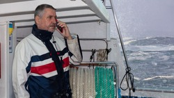 The captain of a small fishing boat is on the phone near the coast. The bearded man looks very determined. But his eyes are absent. Wild waves and spray in the foreground and background.