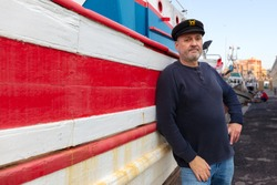 The captain of a very old fishing boat stands in front of his ship. The old wooden boat is painted red and white. The ship is in the harbor in front of a fish hall.