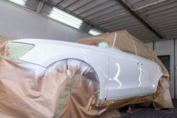 The car after the accident in the camera for car body repair is partially covered with paper and pasted over with green masking tape for painting the side doors and the fender with white color