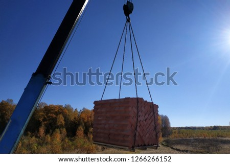 The car crane holds and unloads the brick on the background of the blue autumn sky #1266266152