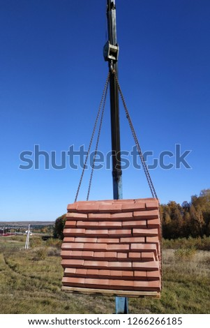 The car crane holds and unloads the brick on the background of the blue autumn sky #1266266185
