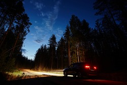 The car drives along a dirt road in the woods against the background of the night sky, brightly lit headlights. Romantic travel and adventure, Side view