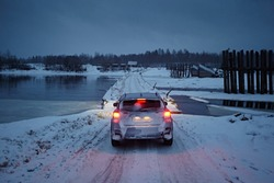 The car drives along a snowy road against the background of the supports of a wooden bridge over the river and a gloomy evening sky in winter.