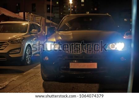 The car headlight on a foggy . Evening-night time . The car on the city road. Evening night time . At night the car burns down the lights #1064074379