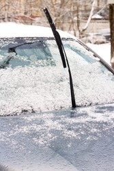 The car in snowdrift with sticking out from under the snow wiper blades