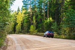 the car is standing on the side of a country dirt road in the forest. Landscape with tall trees. Edge of the forest in early autumn.
