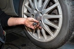 The car mechanic inserts the bolts to screw the cars aluminum rim to the hub.