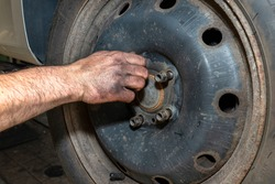The car mechanic inserts the bolts to screw the cars steel rim to the hub.