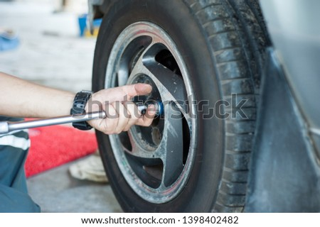 The car mechanic unscrew the nut to remove the car wheel . The car mechanic uses the wrench to tighten the car wheel nut. #1398402482