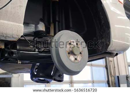 The car on the service is lifted on a lift, the wheel is removed from the car. Rear brake drum and rear suspension.