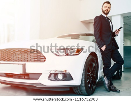 The car shows the character of a man. Confident success elegant business man in full suit and with phone in hand standing near new white sport cabriolet and looks away