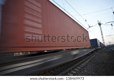 The cargo train moving at great speed by station