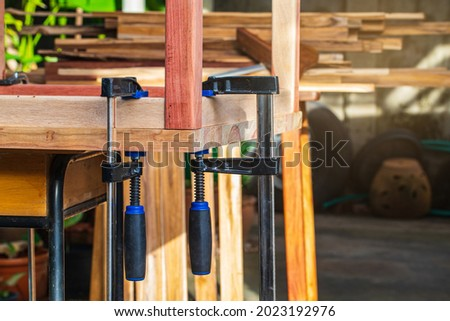 The carpenter uses the F-clamp in his work. Foto stock ©
