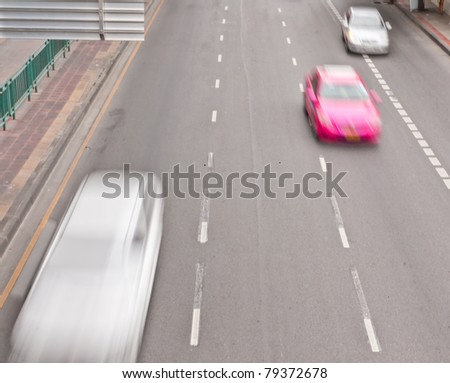 The cars in traffic on the asphalt
