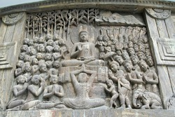 The carving of  Buddha delivering sermon while humble devotees listen attentively in a stupa in Darjeeling, India, Asia