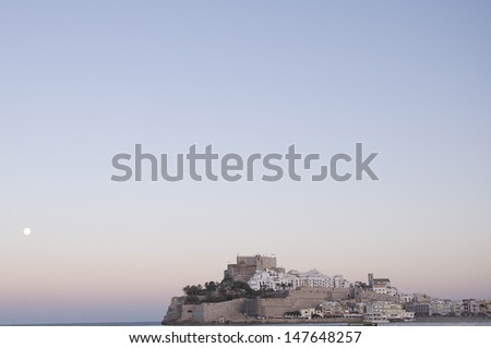 The castle and walls of Peniscola at sunset with a supermoon raising in the sky